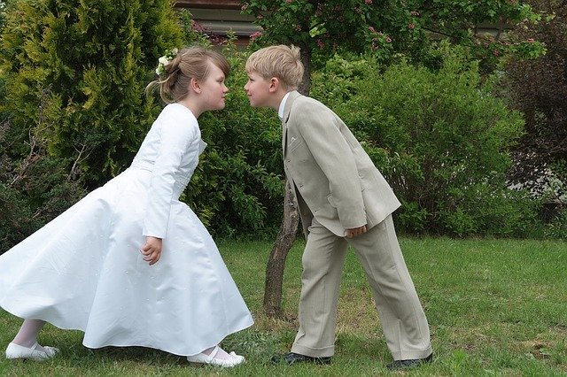 Sex education for kids. Two children in wedding attire trying to kiss each other mouth-to-mouth